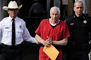 Jerry Sandusky (C) leaves the Centre County Courthouse after being sentenced