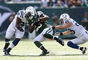 Shonn Greene is tackled by Jerry Hughes #92 and Tom Zbikowski #28 of the Indianapolis Colts