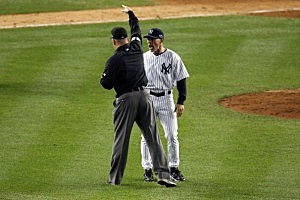 Manager Joe Girardi (R) of the New York Yankees is thrown out of the game by umpire Jeff Nelson out of the game in the eighth inning