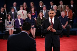 President Barack Obama (R) listens to a question