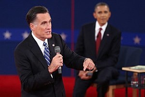 Mitt Romney (L) speaks as U.S. President Barack Obama listens during a town hall style debate at Hofstra University
