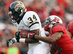 Trayion Durham #34 of the Kent State Golden Flashes is tackled by Marcus Cooper #12 of the Rutgers Scarlet Knights