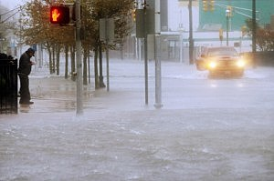A man stands on a dry patch of sidewalk as a vehicle  drives up a flooded street