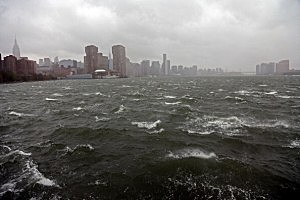 A person walks along the bank of the East River ahead of Hurricane Sandy