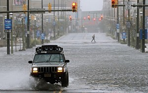 car drives down a flooded street as Hurricane Sandy moves up the coast in Atlantic City, N