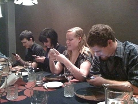 Young diners all using smart phones