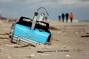A dislodged amusement park bumper car is partially submerged in the sand in Bay Head