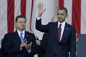 President Barack Obama (R) waves to guests beside US Secretary of Veterans Affairs Eric Shinseki (L) on Veteran's Day at the Tomb of the Unknown Soldier in Arlington National Cemetery