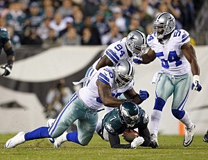 Michael Vick #7 of the Philadelphia Eagles is tackled by Jay Ratliff #90 and DeMarcus Ware #94 of the Dallas Cowboys