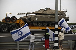 Israeli children wave their national flag as they greet a convoy of tanks passing on a road leading to the Israel-Gaza border near the southern Israeli town of Ofakim