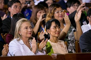 Secretary of State Hilary Clinton (L) listens alongside Aung San Suu Kyi as US President Barack Obama speaks at the University of Yangon