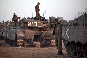 Israeli soldiers prepare weapons and vehicles in a deployment area