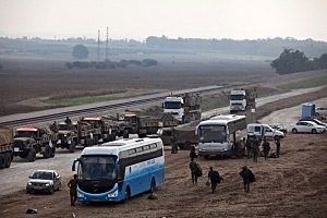 Israeli reserve soldiers and army vehicles depart the Gaza border area