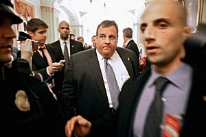 Gov. Chris Christie is surrounded by security and journalists as he walks through the U.S. Capitol