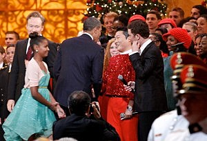 "resident Barack Obama shakes hands with South Korean musician PSY (C), next to host Conan O'Brien (L) and performer Scotty McCreery (R) during the ""Christmas in Washington"" concert at the National Building Museum"