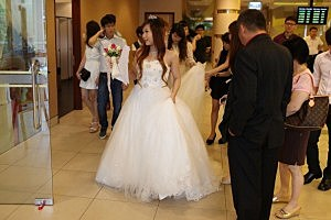 Friends and family assist a bride as she prepares to be married at the Singapore Registry for Marriage on December 12, 2012 in Singapore, Singapore