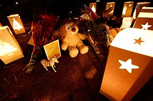 :  Candles surround gifts and flowers that were left in honor of the victims of the mass shooting at Sandy Hook elementary school