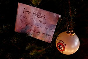 """A note hangs on a tree at a memorial that reads, """"New Milford mourns this tragedy. Our hearts are heavy today,"""" in honor of the victims of the Sandy Hook elementary school shooting"""