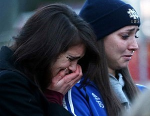 Mourners react at a makeshift memorial near  Sandy Hook Elementary School