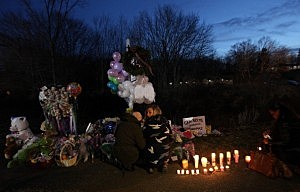 Mourners kneel at a makeshift memorial in Newtown, CT