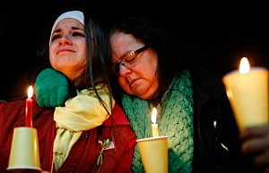 Donna Soto (R), mother of Victoria Soto, the first-grade teacher at Sandy Hook Elementary School who was shot and killed while protecting her students, hugs her daughter Karly while mourning their loss at a candlelight vigil in honor of Victoria at Stratford High School