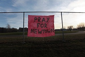A handwritten sign reads 'Pray for Newtown'