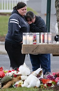 Mourners view a makeshift memorial outside St. Rose of Lima Roman Catholic Church in Newtown, CT