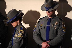 Connecticut State Troopers bow their heads during an interfaith vigil for the shooting victims from Sandy Hook Elementary School