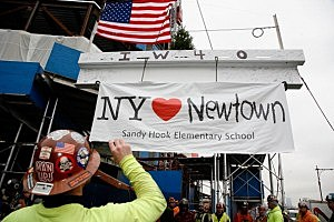 Union workers from Iron Workers Local 40 raise a beam with a banner attached supporting victims of the Newtown, Connecticut school shooting during the Whitney Museum