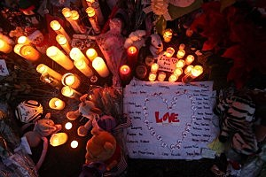 Candles are lit among mementos at a memorial for victims of the mass shooting at Sandy Hook Elementary School,
