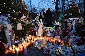 Mourners visit a streetside memorial for 20 children who were killed at Sandy Hook Elementary School o