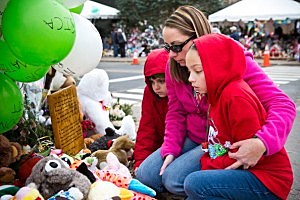 Deborah Gibelli holds her daughter, Alexandra Gibelli, age 9, while looking at a memorial for those killed in the school shooting at Sandy Hook Elementary School,