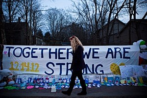 "A woman walks past a sign that reads ""Together we are Strong"" at a memorial for those killed in the school shooting at Sandy Hook Elementary School"