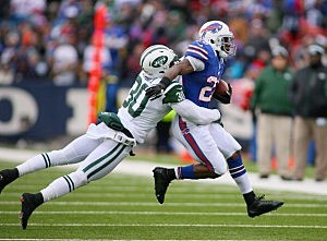 C.J. Spiller of the Buffalo Bills runs with LaRon Landry hanging on