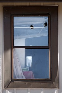 Bullet holes are seen in an upper window of a town home where four people were killed Saturday morning in Aurora, Colorado