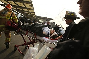 An injured person is carried to a waiting ambulance following a ferry accident at Pier 11 in Lower Manhattan