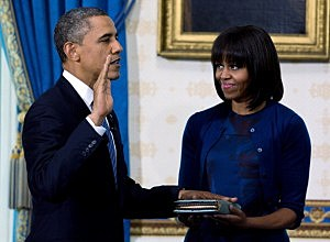 President Barack Obama (L) takes the oath of office as first lady Michelle Obama holds the bible in the Blue Room of the White House