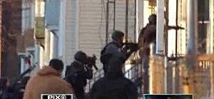 Jersey City Police SWAT team enters a building seeking source of gunshot that injured a woman inside her home