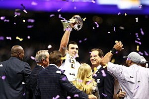 Joe Flacco #5 of the Baltimore Ravens holds up the Vince Lombardi Trophy next to CBS host Jim Nantz