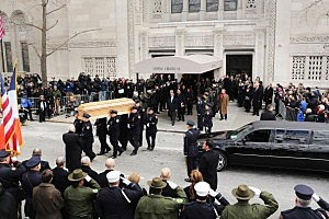 People watch as the casket of former New York City Mayor Ed Koch is brought out by members of the New York Police Department following funeral services at Manhattan's Temple Emanu-El