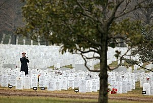 A Bugler plays 'Taps' during a funeral at Arlington National Cemetery