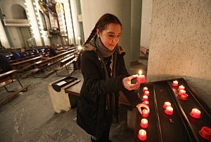 A woman lights a candle at St. Hedwig Catholic cathedral prior to a special evening mass following the announced resignation of Pope Benedict XVI on February 11, 2013 in Berlin, Germany.
