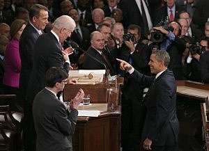 President Barack Obama (R) gestures to U.S. Vice President Joe Biden (L) and Speaker of the House John Boehner (R) before delivering his State of the Union