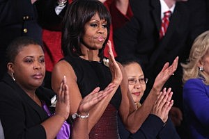 First lady Michelle Obama applauds as U.S. President Barack Obama delivers his State of the Union speech