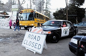 Children board a school bus a day after a standoff between law enforcement officers and who is believed to be suspected murderer and former Los Angeles Police Department officer Christopher Dorner