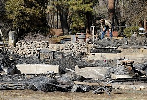 An employee of Southern California Edison surveys the damage at the burned-out cabin where the remains of multiple murder suspect and former Los Angeles Police Department officer Christopher Dorner were found