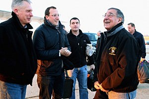 Defense Secretary Leon Panetta (R) talks with USMC Lt. Gen. Thomas Waldhauser (L) and Assistant Press Secretary Carl Woog (2nd L) before boarding the E-4B aircraft on the tarmac at Joint Base Andrews February 20, 2013 in Maryland. Panetta is traveling to Brussels