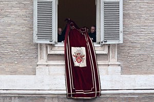 Pope Benedict XVI's personal secretary Monsignor Georg Gaenswein (R) removes the Papal banner from the window after The Pontiff delivered his last Angelus Blessing