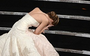 "Actress Jennifer Lawrence trips on her dress after winning the Best Actress award for ""Silver Linings Playbook"