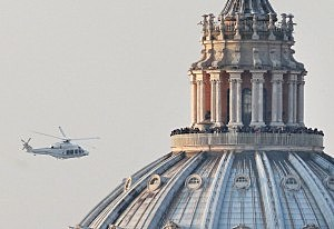 People crowd the gallery on top of St Peter's Basilica as a helicopter carrying Pope Benedict XVI passes by on its way out of Vatican City